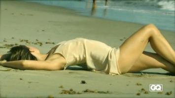 Olivia Wilde laying on sand